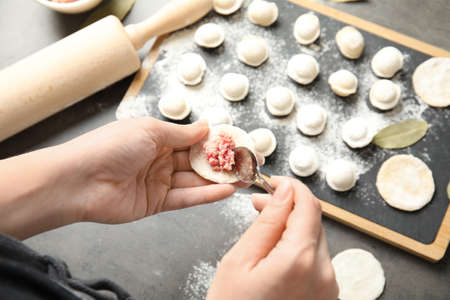 Woman cooking delicious dumplings over table, above view