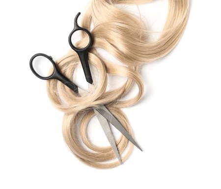 Lockiges blondes Haar und Scheren auf weißem Hintergrund, Draufsicht. Friseurservice