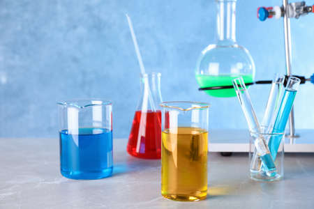Different glassware with samples on table in chemistry laboratory