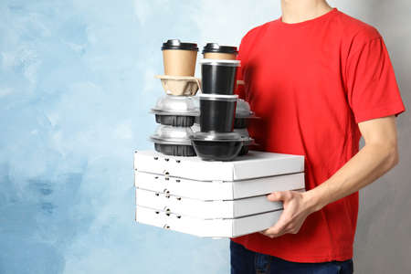 Courier with stack of orders on color background, space for text. Food delivery service 免版税图像