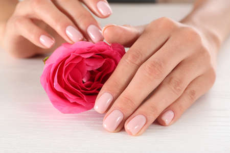 Closeup view of woman with rose at white wooden table. Spa treatment Reklamní fotografie