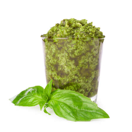 Glass of tasty pesto sauce and basil leaves isolated on white