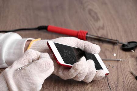 Technician fixing mobile phone at table, closeup. Device repair service Stok Fotoğraf