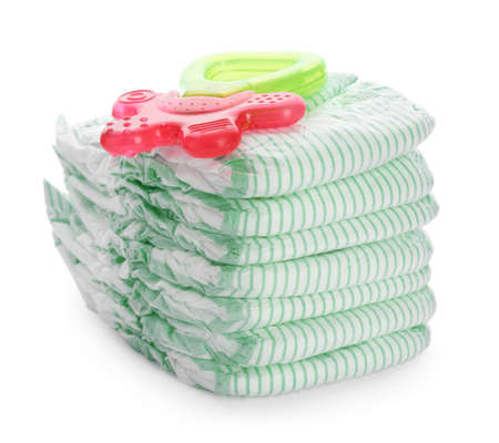 Stack of disposable diapers and teether on white background. Baby accessories Stock Photo
