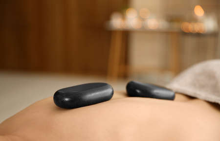 Man receiving hot stone massage in spa salon, closeup. Space for text