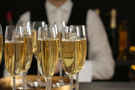 Glasses of champagne and waiter in restaurant, closeup. Space for text Stock Photo