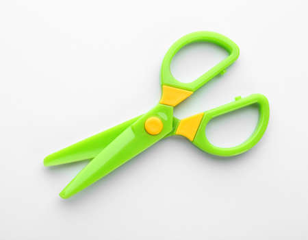 Colorful plastic scissors on white background. School stationery