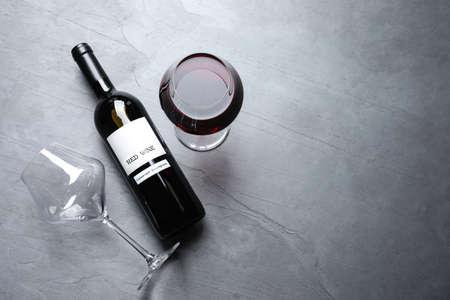 Vasos y botella con vino tinto sobre fondo de color, plano laical. Espacio para texto Foto de archivo