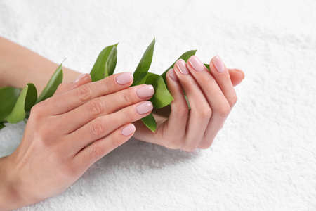Closeup view of beautiful female hands with green leaves on towel. Spa treatment Reklamní fotografie - 121988134
