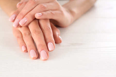 Closeup view of woman with beautiful hands at white wooden table, space for text. Spa treatment Reklamní fotografie