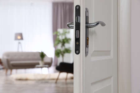 Closeup of open door in modern apartment, space for text