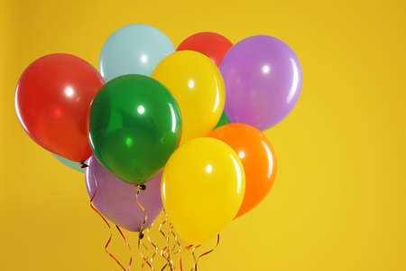 Bunch of bright balloons on color background, space for text. Celebration time Stock Photo