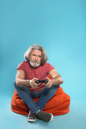 Emotional mature man playing video games with controller on color background. Space for text