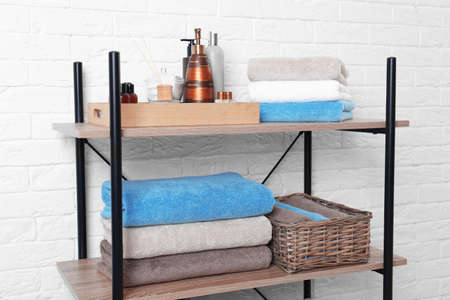 Shelving unit with clean towels and toiletries near brick wall
