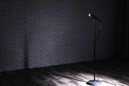 Micrófono en el escenario oscuro cerca de la pared de ladrillo. Espacio para texto Foto de archivo