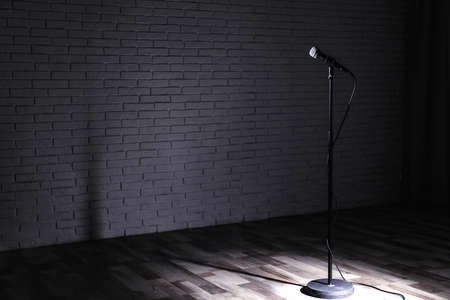 Microphone on dark stage near brick wall. Space for text