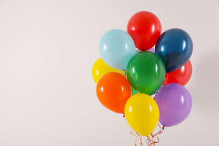 Bunch of bright balloons on light background, space for text. Celebration time