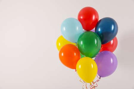 Montón de globos brillantes sobre fondo claro, espacio para texto. Hora de celebrar