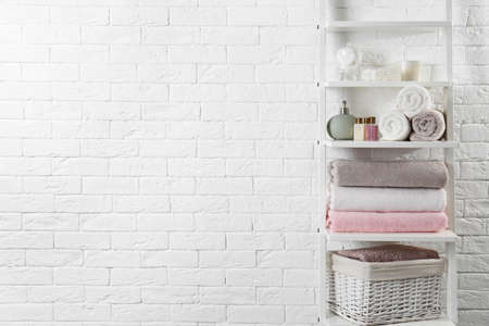 Shelving unit with clean towels and toiletries near brick wall. Space for text