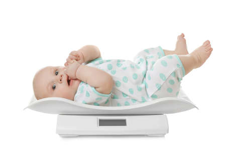 Cute little baby lying on scales against white background 版權商用圖片