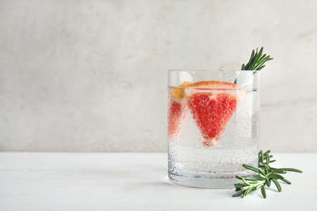 Glass of infused water with grapefruit slices on table. Space for text