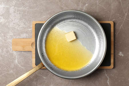 Frying pan with melting butter on grey background, top view