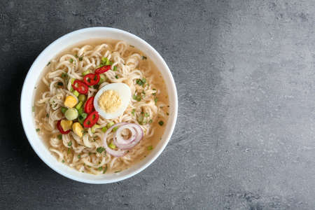 Bowl of noodles with broth, egg and vegetables on grey background, top view. Space for text