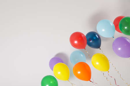Different bright balloons on light background, space for text. Celebration time 免版税图像