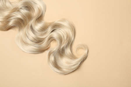 Lock of blonde wavy hair on color background, top view. Space for text