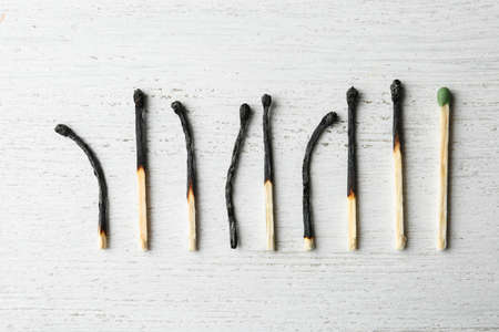 Row of burnt matches and whole one on wooden background, flat lay. Uniqueness concept