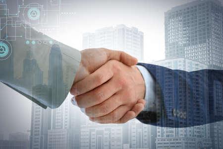 Businessmen shaking hands against cityscape, closeup. Double exposure