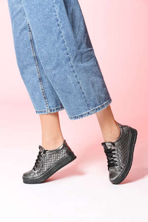 Woman in stylish shoes on color background, closeup