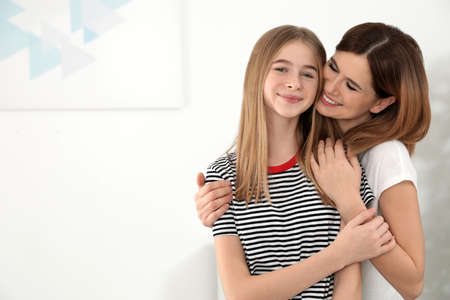 Happy mother hugging her teenager daughter at home