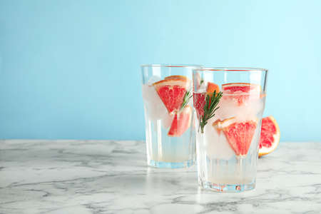 Glasses of infused water with grapefruit slices on table against color background. Space for text