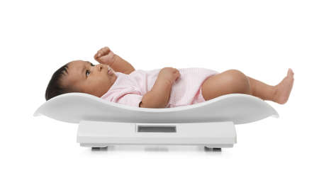 African-American baby lying on scales against white background