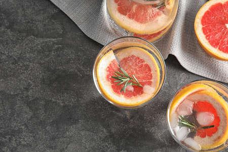 Vasos de agua infundida con rodajas de pomelo en mesa gris, plano laical. Espacio para texto