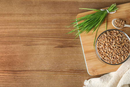 Bowl with seeds and wheat grass on wooden background, flat lay. Space for text
