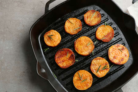 Grill pan with sweet potato fries on grey background, top view
