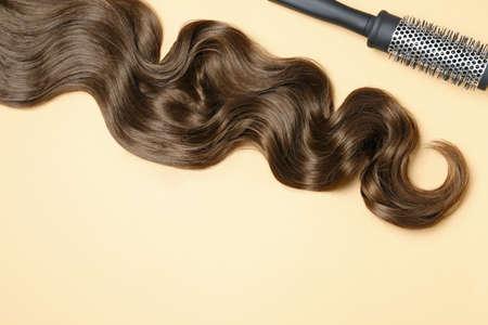 Serrure de cheveux bruns ondulés et brosse sur fond de couleur, mise à plat. Espace pour le texte Banque d'images