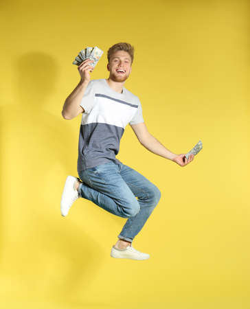 Young man jumping with money on color background Zdjęcie Seryjne