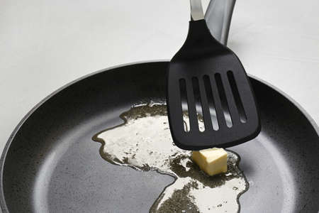 Frying pan with melting butter and spatula on table, closeup