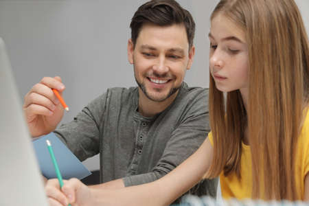 Father helping his teenager daughter with homework indoors