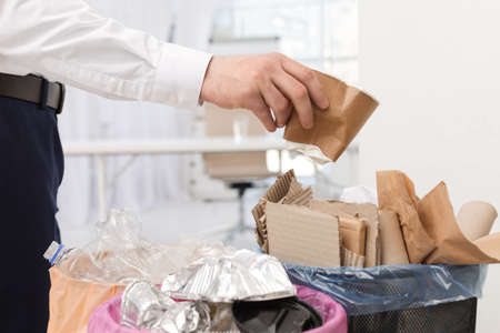 Man putting used paper cup into trash bin in office, closeup. Waste recycling Standard-Bild - 122349618