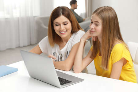 Happy mother and her teenager daughter with  laptop at home
