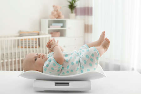 Cute little baby lying on scales in light room