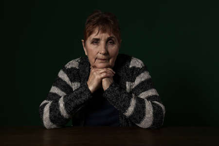 Poor senior woman sitting at table against color background