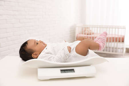 African-American baby lying on scales in light room