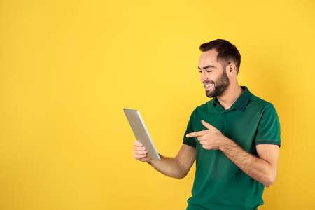 Uomo che utilizza tablet per chat video su sfondo colorato. Spazio per il testo