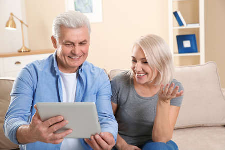 Mature couple using video chat on tablet at home