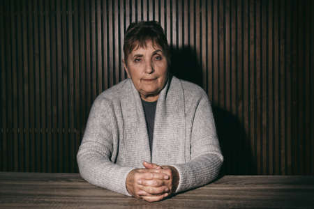 Portrait of poor senior woman sitting at table against wooden wall Stock Photo